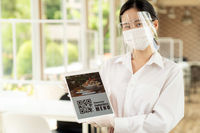 New Normal asian waitress hold qr code contactless menu tablet