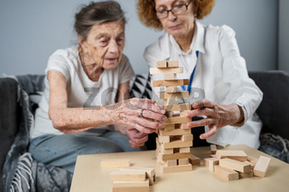 Jenga game. Theme is dementia, aging and games for old people. Caucasian senior woman builds tower of wooden blocks with the help of a doctor as part of a therapy and jenga game at a patient's home