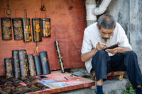 Old chinese man sketching picture with pencil