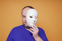 man taking off mask revealing face and identity
