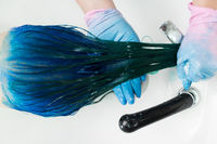 Top view of hairdresser washes client's head with long hair sapphire color after hair coloring process
