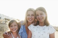 Happy mother and daughters on beach
