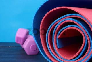 neoprene blue and ren twisted mat lies on a blue wooden background,