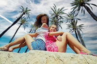 Happy mother and 8s daughter sit under cloudy blue sky and palm trees