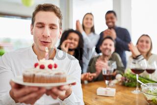 Mann pustet Kerze aus auf Kuchen bei Geburtstagsfeier am Esstisch mit Freunden