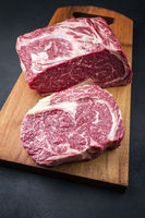 Raw dry aged wagyu entrecote beef steak roast as top view on a modern design wooden board
