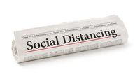 Rolled newspaper with the headline Social Distancing