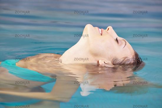 Lachende Frau bei Entspannung im Wasser