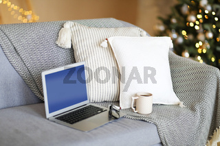 Laptop on sofa in room with festive lights of the Christmas tree
