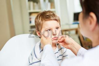 Kinderärztin tastet Mandeln und Lymphknoten