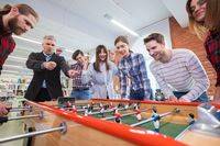 Business people playing table football