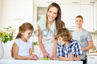 Glückliche Familie schneidet Obst in Küche