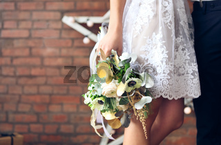 Cheerful married couple with wedding bouquet