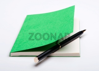 Green notebook and ballpoint pen