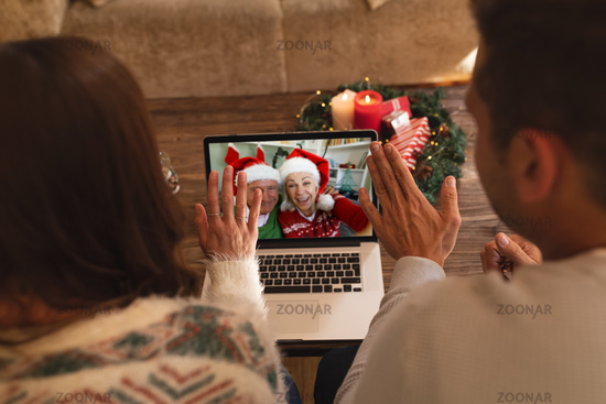 Rear view of couple waving while having a videocall with senior couple in santa hats smiling on lapt