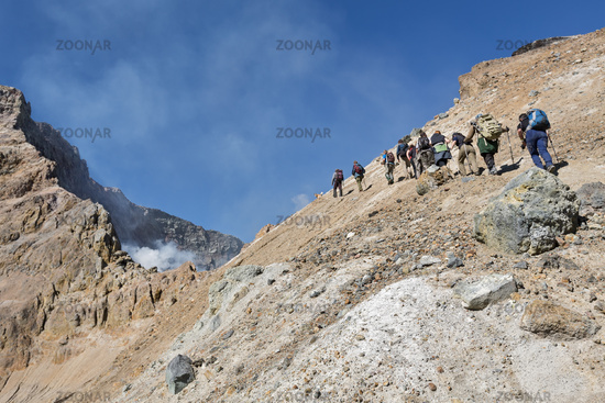 Group of tourists climbing on crater active volcano. Kamchatka Peninsula