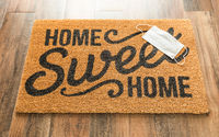 One Medical Face Mask Rests on Home Sweet Home Welcome Mat Amidst The Coronavirus Pandemic