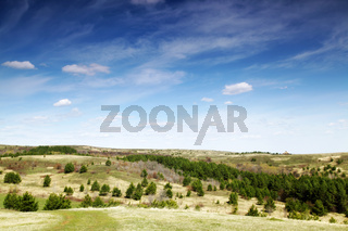 landscape with green hills and blue sky.