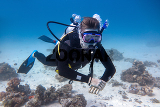 Young diver floats underwater in the sea
