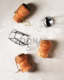 Champagne Corks Still Life: Used corks and wire cages and caps on a light gray mottled surface.
