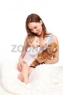 Mutter und Kind spielen mit dem Teddy