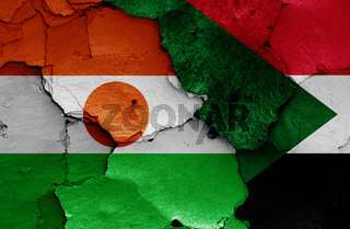 flags of Niger and Sudan painted on cracked wall
