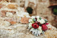 Wedding bouquet on the broken brick fence. Blurred background