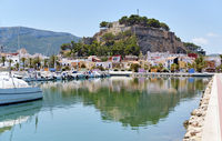Waterside view to moored yachts at harbour, old famous Denia Castle located on rocky hilltop mountain. Heart of ancient city, landmark and tourism concept. Alicante province, Costa Blanca, Spain