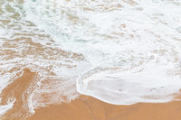Ocean coast, moviment white foam on sand.