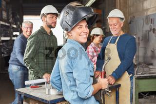 Frau als Schweißer im Team einer Schlosser Werkstatt