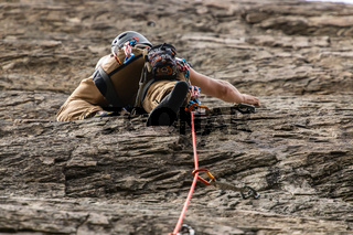 Traditional outdoor rock climber ascends