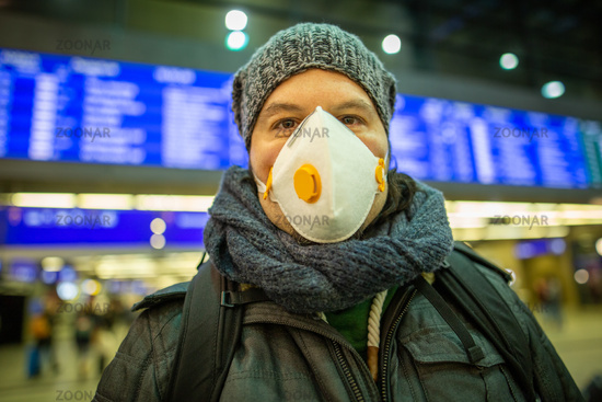 Man wearing a respirator mask device for health protection at an airport or railway train station in a crowd of people while travelling. Epidemic corona virus infection, flu sickness and travel illness concept.