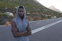 Portrait of fit african american man in sportswear standing on a coastal road