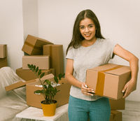 Beautiful hispanic female standing with box in new home