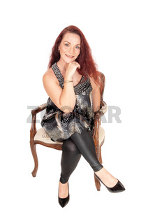 Gorgeous woman sitting in an old chair, hand under chin