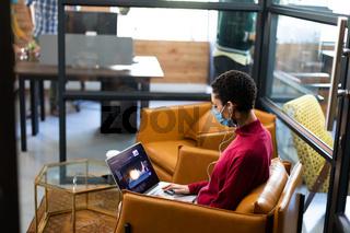 Mixed race woman wearing face mask working on laptop wearing earphones in casual office