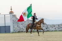 A Very Handsome Mexican Charro Poses In Front Of A Hacienda In The Mexican Countryside While Holding The Mexican Flag