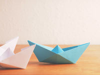Teamwork business concept with paper boat on a wooden table