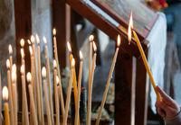 Person  flaming a Church candles in a church