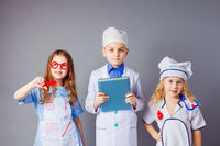 Cute little children dressed as doctors on grey background.