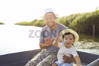 Father and little son in hats on fishing