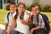 Young Hispanic Student Children Wearing Backpacks On School Campus