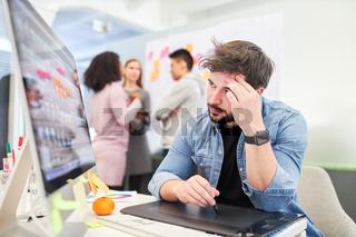 Webdesigner sitzt erschöpft  am Computer