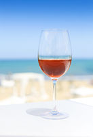 Glass of rose wine against blue water and sea