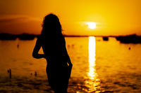A Lovely Nude Latin Model Is Silhouetted As She Poses With The Rising Sun Behind Her On A Romantic Caribbean Beach