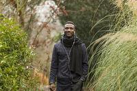 Happy Black Man with Earphones Posing in Park
