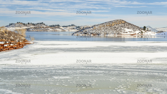 Partially frozen calm lake at foothills of Rocky Mountains