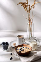oatmeal with blueberries, milk and cup of coffee