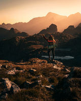 hiker relaxing on the mountain and watching sunset over the valley in austria