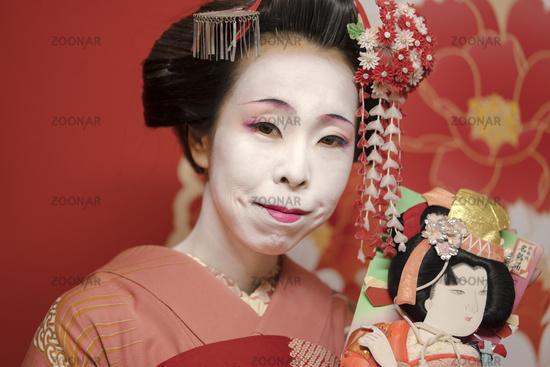 Maiko in a kimono with kanzashi pins and holding a hagoita racket.